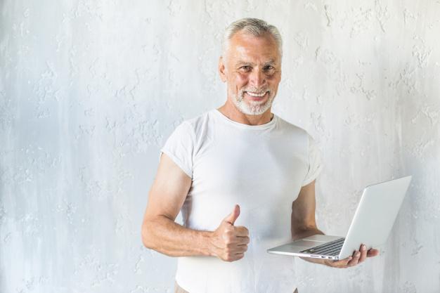 sorrindo-homem-senior-segurando-laptop-mostrando-polegar-cima-sinal_23-2147859874
